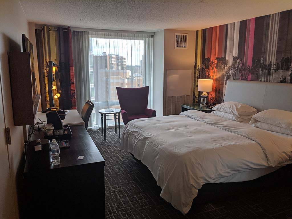 Hotel room with big double bed, chair and a lot of decoration (Hyatt Centric Arlington)
