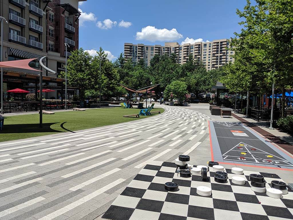 Pentagon Row Central Plaza, chess field in the foreground, neighborhood in the background. Green areas with seating and games.